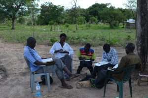 John (white shirt) reading scripture from Mark 5:1-20 during IAS small group disciplship training in Gilumbi
